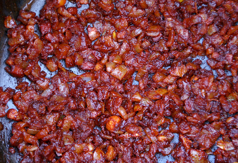 В гарячий жир з підсмаженою цибулею всипати червону паприку і швидко перемішати